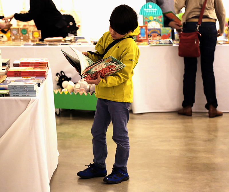 Young boy reading a book at The London Children's Book Fair at Parasol unit
