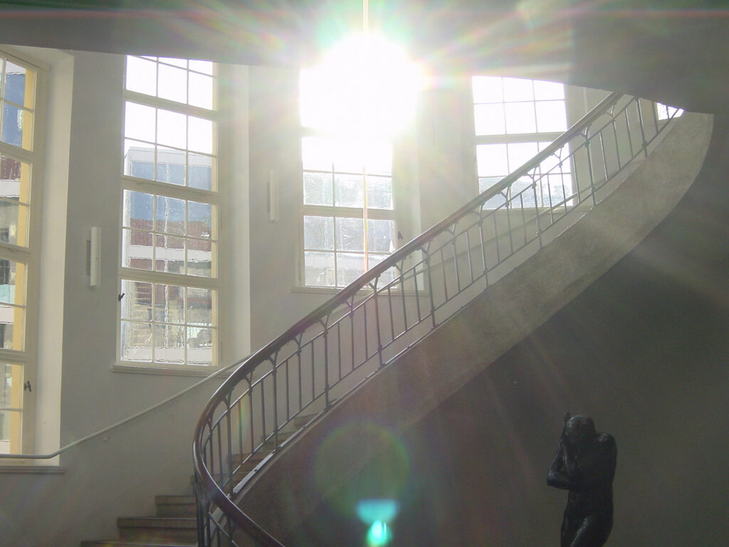 Sunlight through a window shining on a statue by Rodin