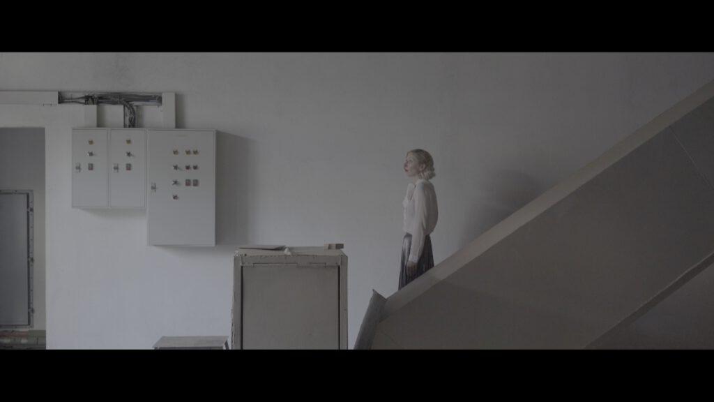A woman walking down a dimly lit staircase